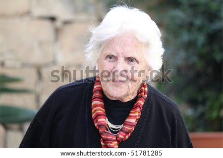 an old caucasian woman wearing a scarf and cardigan contemplating about something - stock photo