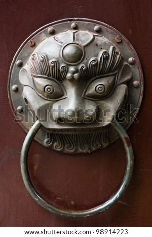 an old Chinese style door handle on a red door - stock photo