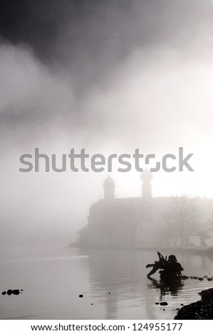 An old Church on a calm lake, barely visible through the dense Fog in the morning. - stock photo