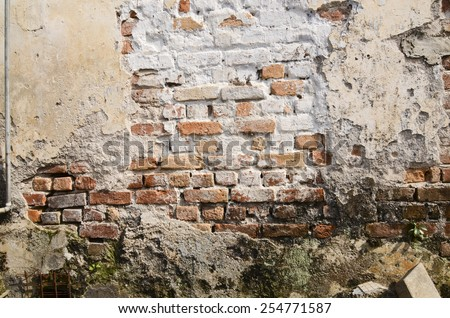 An old colonial township with some defaced brick walls among them / Old brick wall / Grunge and fallen plaster exposing bricks within - stock photo