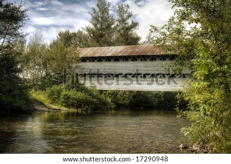 An old covered bridge wit a rusty roof in the forest - stock photo
