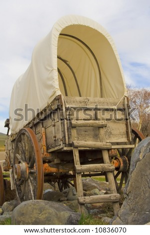 An old covered wagon sits on a rocky patch of ground. - stock photo