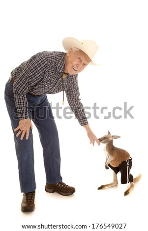 An old cowboy reaching down to a baby kangaroo. - stock photo