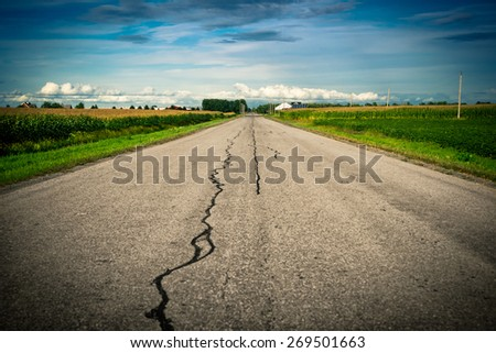 An old cracked, damaged and repaired country asphalt road stretches ahead toward its vanishing point on the distant horizon with corn fields on either side. - stock photo