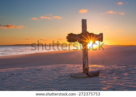 An old cross on a sand dune next to the ocean with a calm sunrise - stock photo