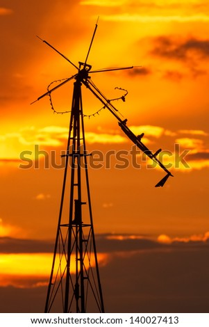 An old decrepit windmill is silhouetted by a brilliant sky at sundown. - stock photo