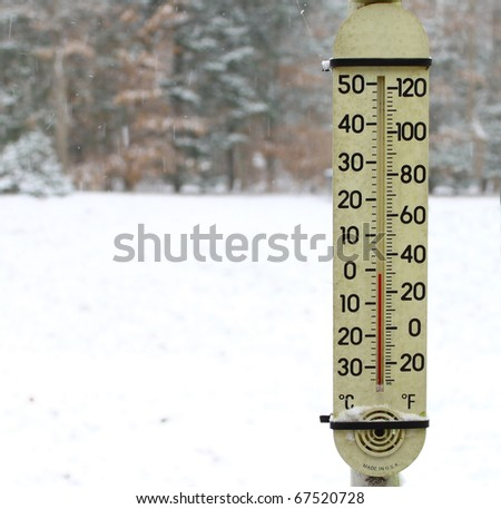 An old dirty red mercury thermometer covered with snow strapped on a post outside using a shallow depth of field and selective focus with room for your text. - stock photo