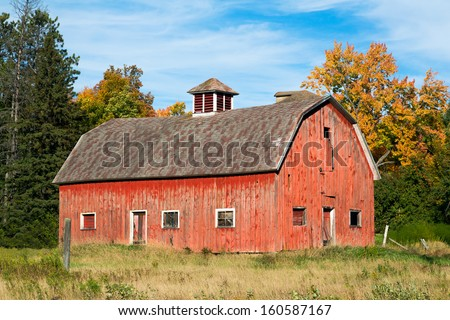 An old faded red barn in rural Wisconsin stands beneath a cloud-draped blue sky with fall foliage. - stock photo