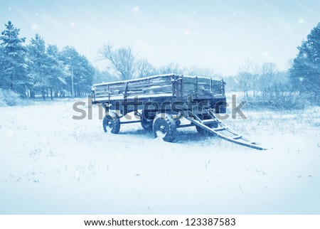 an old farm cart in the snow - stock photo