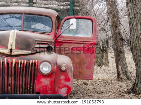 An old  farm truck abandoned in some trees - stock photo