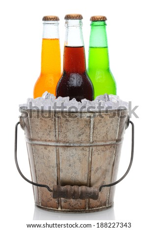 An old fashioned bucket filled with ice and soda bottles. Three different pop bottles are represented, orange, cola and lemon lime. Vertical format on a white background with reflection. - stock photo