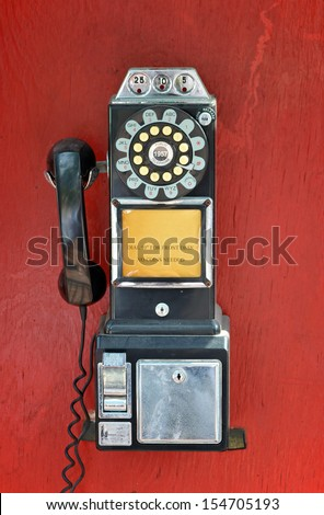 An old fashioned pay phone against a red background - stock photo