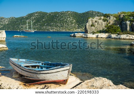 An old fishing boat moored at Simena peninsula with an ancient island Kekova on a background - stock photo