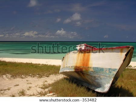 An old fishing boat on a caribbean beach... - stock photo