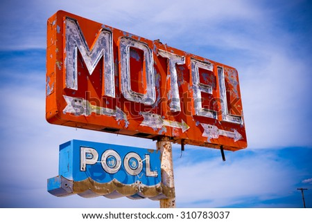 An old, flaking neon motel sign in the American Desert.  Abandoned signage. - stock photo