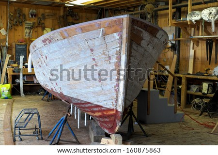 an old 26 foot lobster boat is completely disassembled and in the process of refinishing inside an old boat shop - stock photo