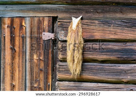 An old goats beard hung out to dry outside a wooden building beside hinge. - stock photo