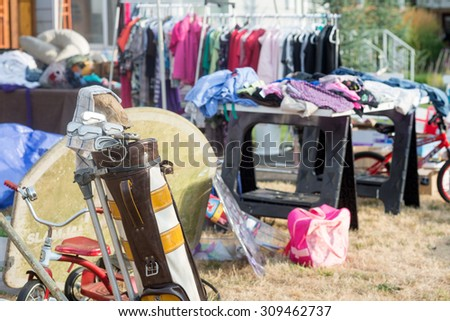 An old golf bag filled with clubs at a yard sale with a jumble of clothing and toys in the soft background - stock photo