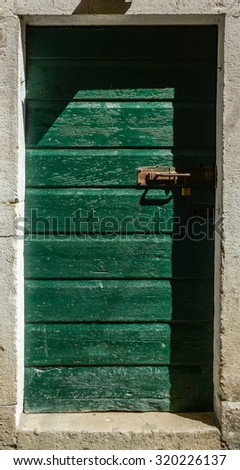 an old green ragged shabby wooden door - stock photo