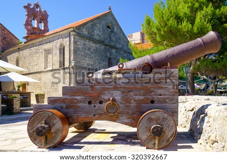 An old gun on the city walls, and the All Saints Church, in the old town of Korcula, Croatia - stock photo