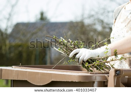 An old hand of active senior with white gloves composting twigs and a lot of others garden things; doing spring / summer work on garden (fous on hand) - stock photo