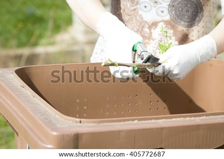 An old hand of active senior with white gloves composting twigs and a lot of others garden things; doing spring / summer work on garden (fous on scissors) - stock photo