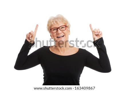 An old happy lady pointing on a copy space. isolated on white.  - stock photo