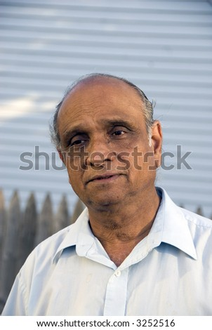 An old indian man smiling in the summer sun - stock photo