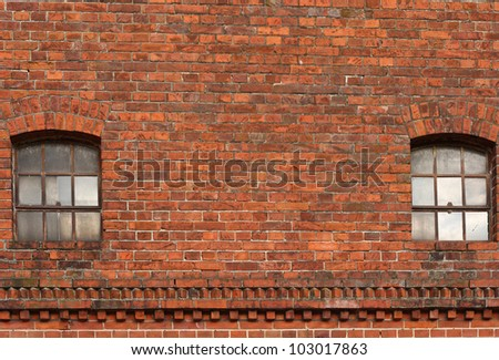 an old industrial wall made of red brick stones with two windows made of glass - stock photo