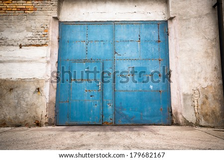an old iron door closed with brick wall - stock photo