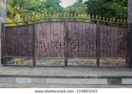 an old iron gate in front of a house in Bali - stock photo