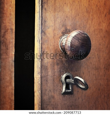 an old iron key in the lock of the door - stock photo