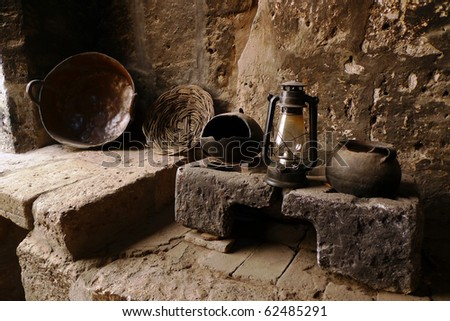 An old kitchen with pots, lamp and plate - stock photo