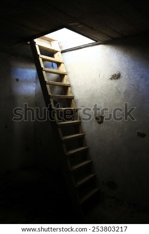 An old ladder in an underground room - stock photo