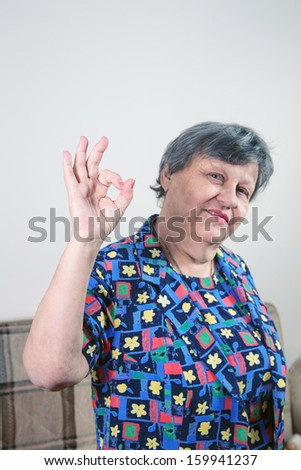 an old lady making okay sign - stock photo