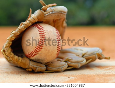 An old leather baseball mitt, or glove with a worn baseball laying on a home plate. There is clay around. Home plate needs to be dusted off. Shallow depth of field. Horizontal composition. Copy space - stock photo