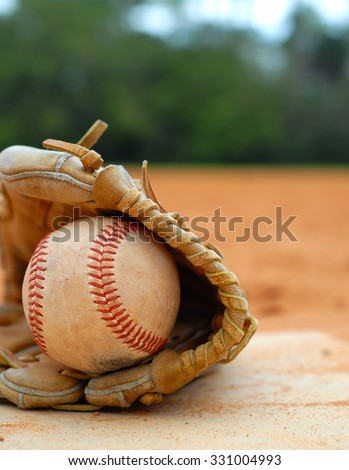 An old leather baseball mitt, or glove with a worn baseball laying on a home plate. There is clay around. Home plate needs to be dusted off. Vertical composition with copy space upper right. - stock photo