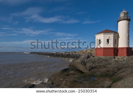 An old lighthouse on a rock pacific coast shoreline. - stock photo