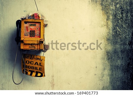 An old looking public phone on a rusty wall - stock photo