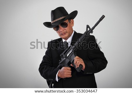 An old mafia in black suit and cowboy hat posing with an assault weapon - stock photo