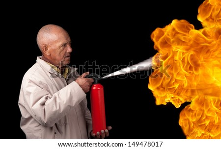 An old man attempts to extinguish the flames of a giant fire with a small extinguisher. - stock photo