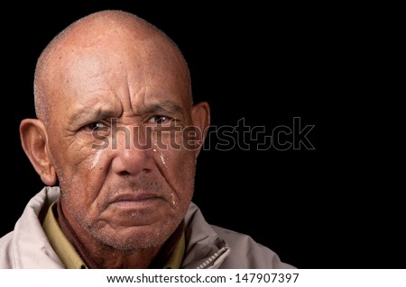 An old man cries whilst staring aimlessly. - stock photo