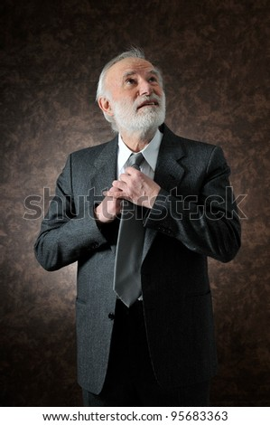 an old man fixes his tie in studio - stock photo