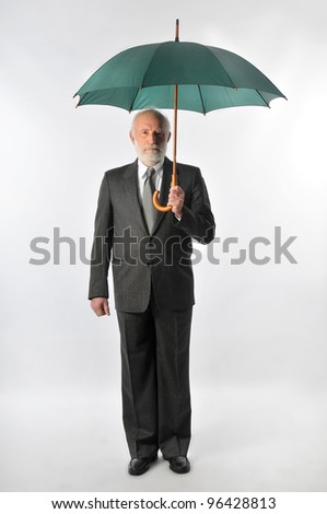an old man holds an umbrella - stock photo