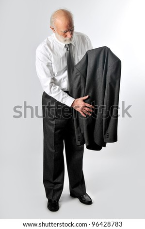 an old man holds his jacket - stock photo