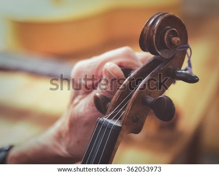 An old man (luthier) with aged hands is tuning a violin. You see other instruments like a guitar blurred in the background.  - stock photo