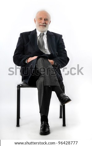 an old man sits in black chair - stock photo