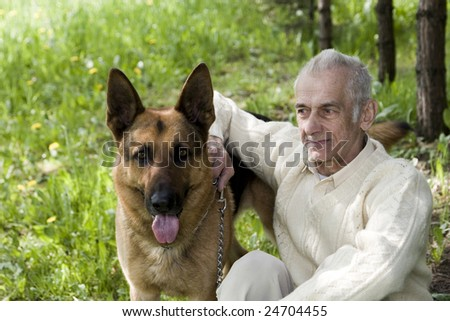 An old man who is sitting on nature with his dog. - stock photo
