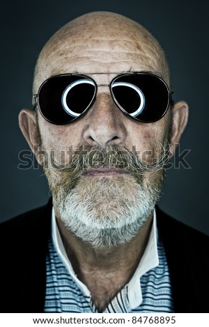 An old man with a grey beard wearing sunglasses - stock photo
