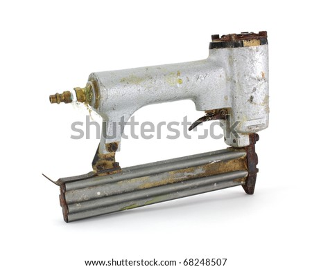 An old nail gun used for brads on a white background. - stock photo